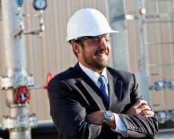Hispanic businessman (30s) standing outside industrial building.